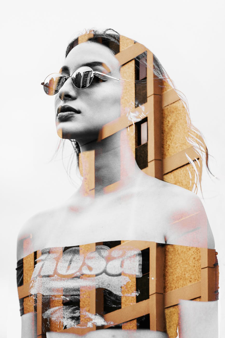 a woman wearing sunglasses pasted on a building wall